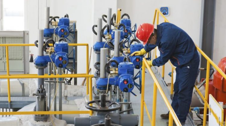 Engineer checking the oil pipeline equipment in crude oil storage workshop, Beijing, China.
